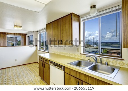 Empty Kitchen Room With Linoleum Floor, Old Storage Cabinets And White  Appliances. View Of