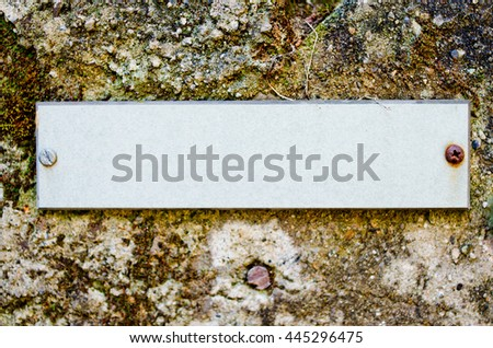 empty  label with rusty screws on old wall - stock photo