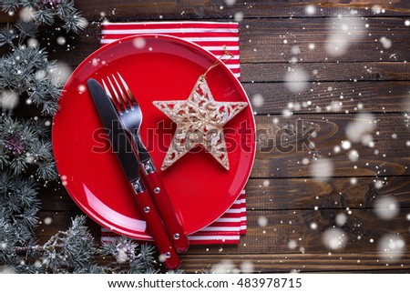 Empty late, knife and fork, napkin and christmas decorations in white and red colors on dark wooden table. Drawn snow effect. Christmas table setting.Top view. Place for text. Selective focus.