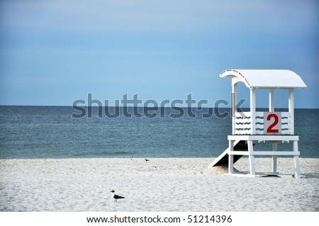Empty lifeguard hut and seagulls on deserted beach. - stock photo