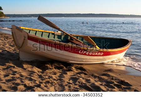 Empty lifeguard rowboat on beach at sunset