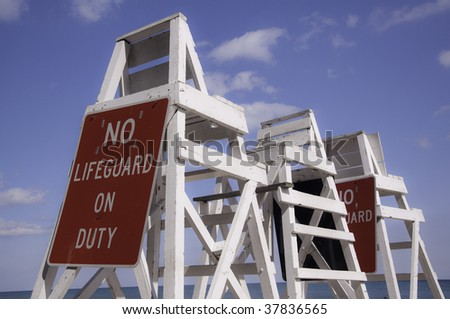 Empty lifeguard tower chair with not on duty sign - stock photo