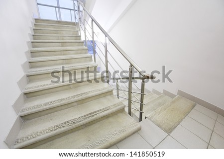 Empty light and simple staircase with metal railings and white walls. - stock photo