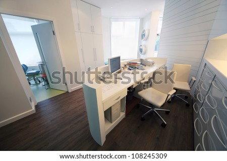 Empty lit reception area in dental clinic. Working place at table with computer. - stock photo