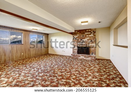 Empty living room with brick fireplace, wooden plank paneled wall and colorful carpet floor - stock photo