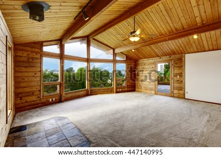Empty living room with carpet floor in wooden trim house with large windows and balcony door - stock photo