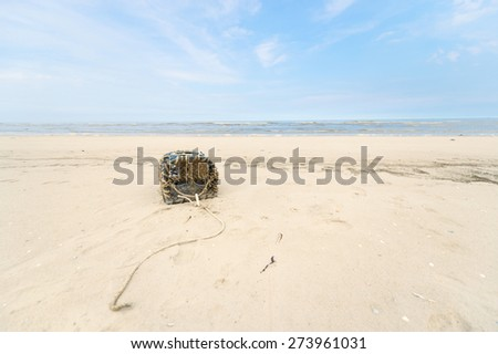 Empty lobster trap on the beach  - stock photo