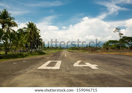 Empty local airport of Quepos in Costa Rica with the mountains and the forest in the background. On the run away, the letters 04 are displayed in a large format. - stock photo