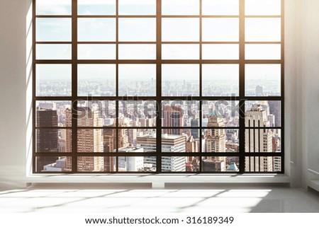Empty loft interior with city view - stock photo