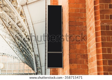 Empty long vertical display sign on bricks wall  - stock photo