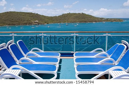 Empty lounge chairs overlook blue water and a tropical island - stock photo