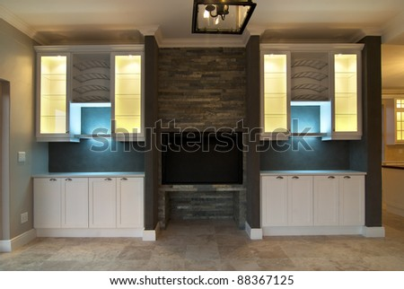 Empty lounge inside a modern house with some lights turned on - stock photo