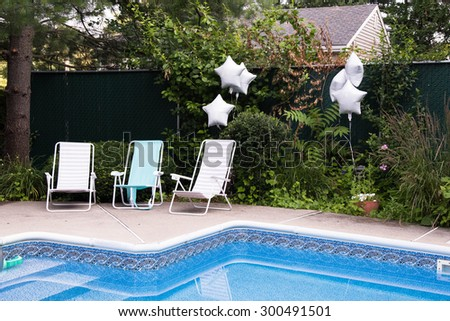 Empty loungers at the backyard pool waiting for party guests to arrive - stock photo