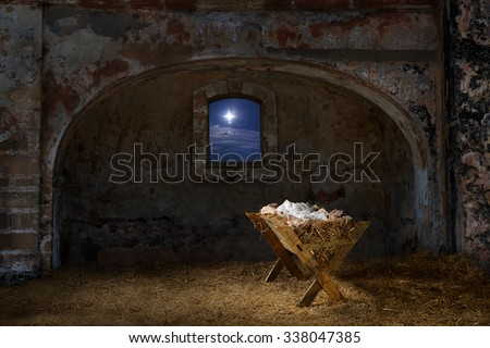 Empty manger in old barn with window showing the Christmas star