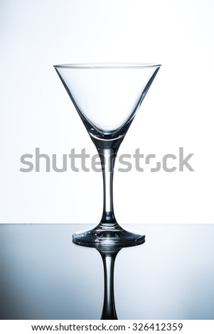 empty martini glass on the glass table and white background