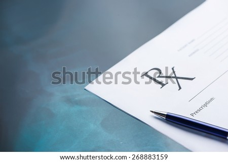 Empty medical prescription with a pen on blue reflective background - stock photo