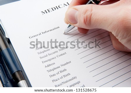 Empty medical questionnaire in a clipboard with a hand holding a pen - stock photo