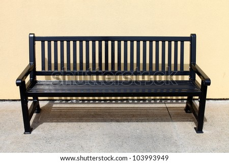 Empty metal bench in sunshine - stock photo