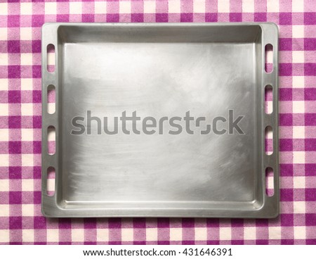 Empty metal oven tray on lilac background