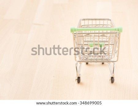 Empty metal shopping basket on wood surface. Conceptual image of retail store, sale and commerce. - stock photo