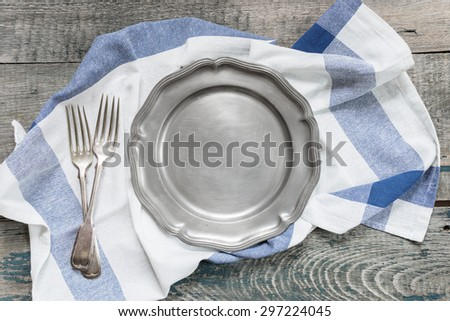 Empty metal utensils and kitchen towel on a rough wooden table, top view