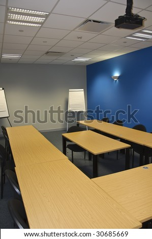 empty modern classroom or meeting room with flip boards and overhead projector - stock photo