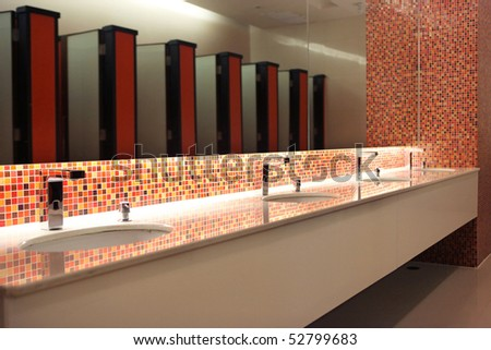 Empty modern restroom interior with washstands and toillets in mirror - stock photo