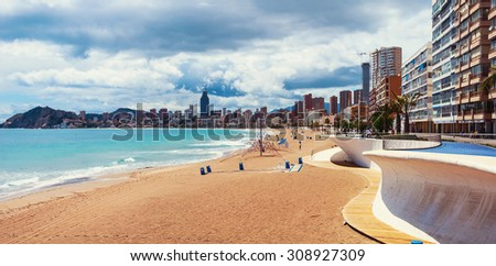 Empty morning beach in Benidrom, Costa Blanca, Spain in spring. Skyscrapers and heavy clouds at the background. Popular touristic resort with a beautiful coastline - stock photo