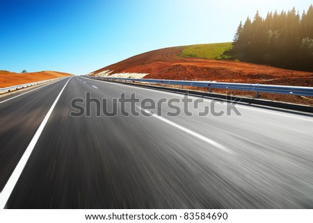 Empty motion blurred asphalt road through hills with red soil and clear blue sky - stock photo