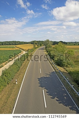 empty motorway surrounded by bushes - stock photo