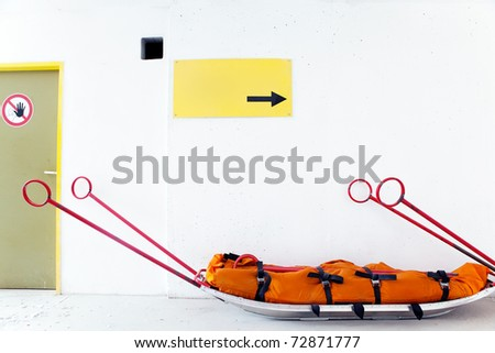 "Empty mountain rescue sled for injured skiers, snowboarders or mountain climbers, danger sign ""STOP!"" and blank yellow caution board in front of white wall background - stock photo"