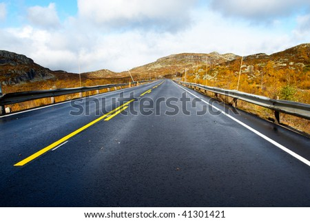 empty mountain road road receding into the distance at the cloudy autumn day - stock photo