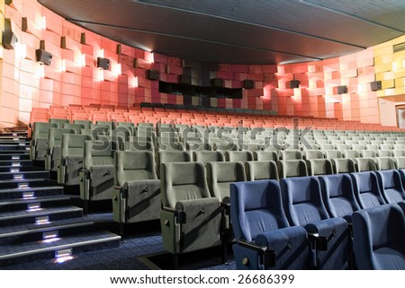 Empty new cinema auditorium with rows of blue, gray and red chairs and illuminated stairs.