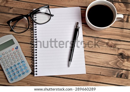 Empty notebook and office supply on table - stock photo