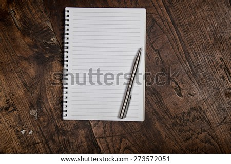 Empty notebook and pen on wooden background look old or vintage style. - stock photo