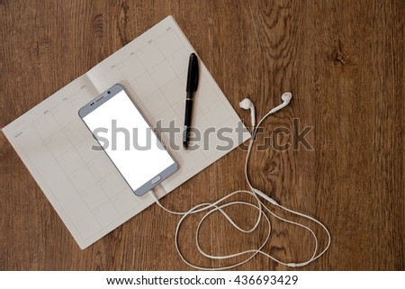 Empty notebook and phone  on wood background.  - stock photo