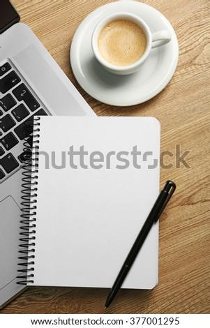 Empty  notebook on laptop keyboard, on light background - stock photo