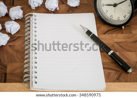 Empty notebook on wooden table with crumpled papers around - stock photo