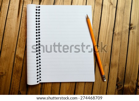 Empty notebook with crayon on table - stock photo