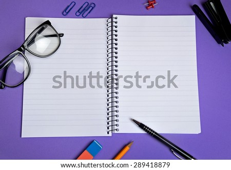 Empty notebook with office supply on purple background - stock photo