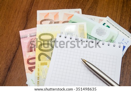 empty notebook with pen and euro banknote on wood table