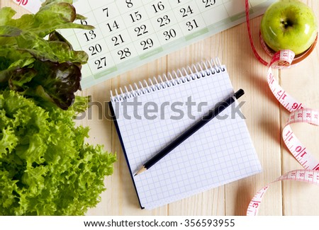 Empty notebook with vegetable salad and apple ,  calendar on wooden table - stock photo