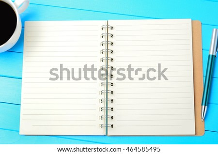 Empty notepad with coffee and pen on wooden table