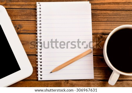 Empty notepad with coffee and tablet on table - stock photo