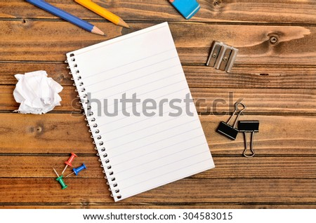 Empty notepad with office supply on table - stock photo