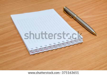 empty notepad with pen on table - stock photo