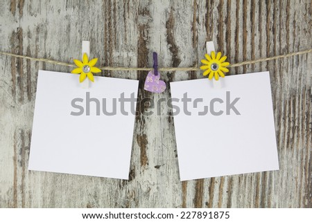 Empty notes and heart hanging with a clothespin, in a wood background