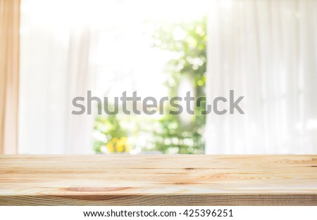 Empty of wood table top on blur of curtain window and abstract green from garden with sunlight .For montage product display or design key visual layout - stock photo