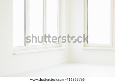 Empty off-white room with large windows and light wooden floor. - stock photo