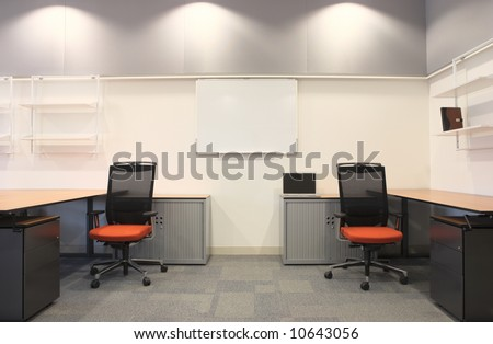 Empty office with new modern office furniture, including desks, cupboards, filing cabinets and chairs. Two orange chairs facing out. HDR type image